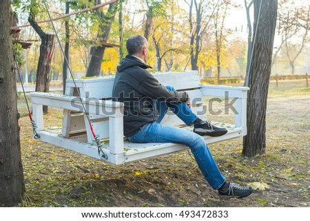 Man is sitting on swing in the autumn park, relaxing and dreaming. Back view.