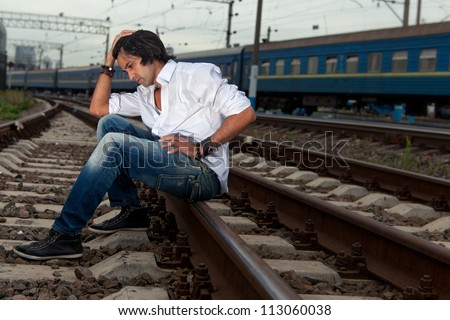 Man is sitting on the rails of the railway station - stock photo