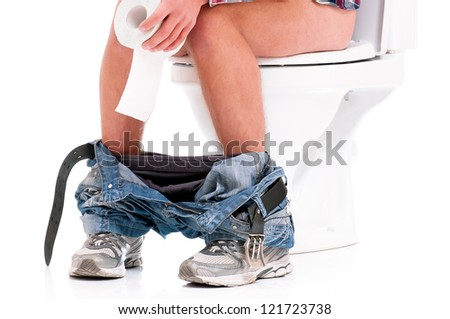 Man is sitting on the toilet bowl, holding paper in hands, on white background - stock photo