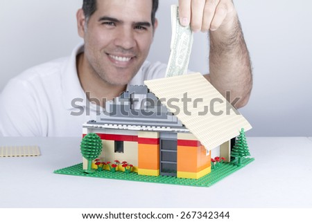 Man is smiling while use a assembled house like a box savings - stock photo