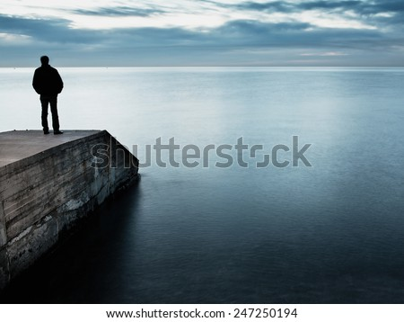 Man is standing on a jetty looking the sunset - stock photo