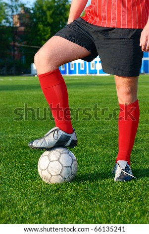 man is standing on football field with ball - stock photo