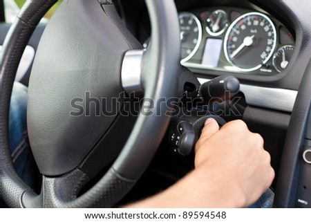 Man is starting his car; he is turning the ignition key under the wheel - stock photo