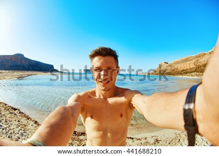 man is sunbathing on the sand on the beach. Male partially in water, taking selfie - stock photo