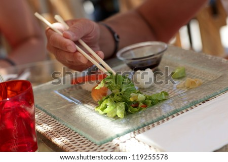 Man is taking lettuce by chopsticks in a japanese restaurant