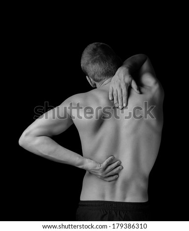 Man is touching the back, concept of pain in the spine, monochrome image - stock photo