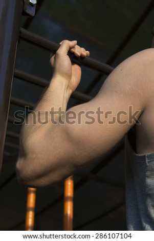 Man is training on the horizontal bar, strong body