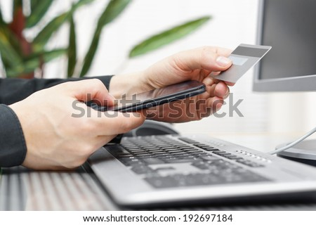 Man is using credit card and mobile phone for  on line payment. mobile  shopping concept - stock photo