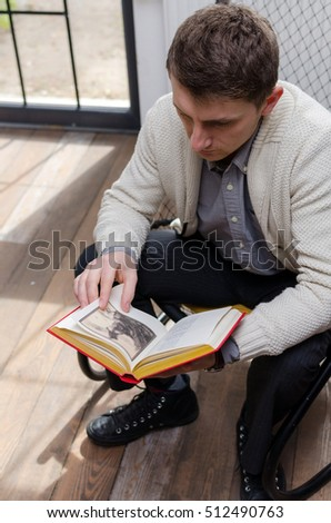 Man is viewing an illustration in the book