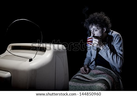 man is watching tv with legs covered and a cup of the in the hand - stock photo
