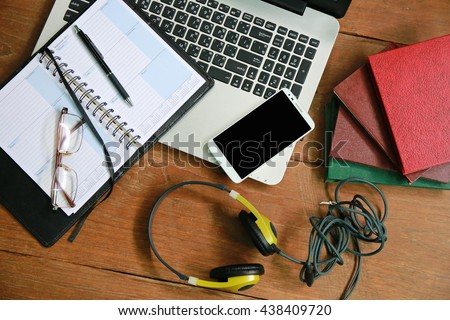 man is working by using a laptop computer on wooden table. Hand typing on a keyboard.Layout of comfortable working space on wooden, internet laptop headphone phone notepad pen eyeglasses laying on it  - stock photo