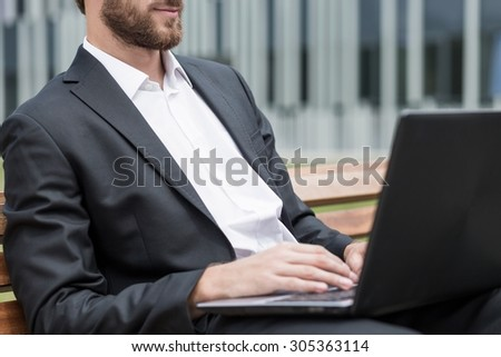 Man is working on computer outside of company - stock photo
