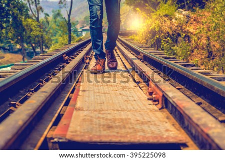 Man jeans and sneaker shoes walking on Railroad - stock photo
