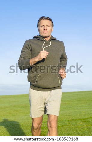 man jogging in park wearing a grey sweatshirt and shorts. - stock photo