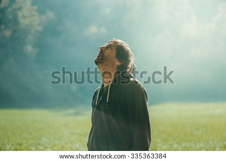 Man jogging in the park, standing and looking up, early autumn morning, sport, recreation and healthy lifestyle concept, retro toned image with selective focus - stock photo