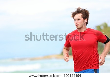 Man jogging on beach. Male runner running listening to music on mp3 player or smart phone. Young caucasian male fitness sport model in red t-shirt. - stock photo