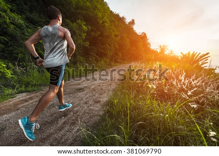 Man jogging on the gravel road at sunset - stock photo