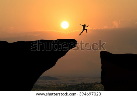 Man jump through the gap between hill.man jumping over cliff on sunset background,Business concept idea - stock photo