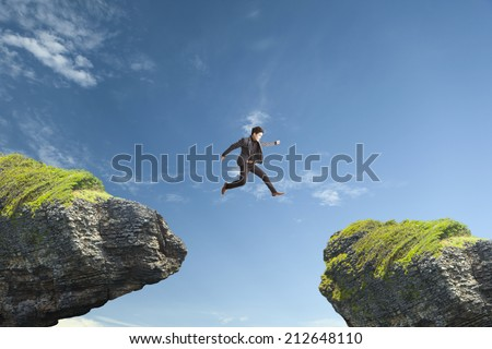 man jumping across peak. - stock photo