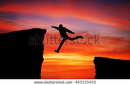 Man jumping across the gap from one rock to cling to the other. Element of design.