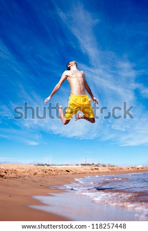 Man Jumping Against Blue Sky on the Beach