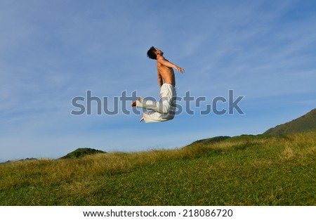 Man jumping against sea and mountain with blue sky