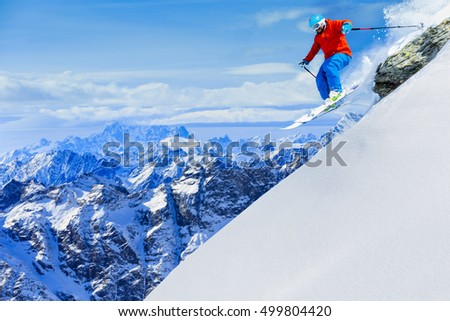 Man jumping from the rock, skiing on fresh powder snow with swiss alps in background.