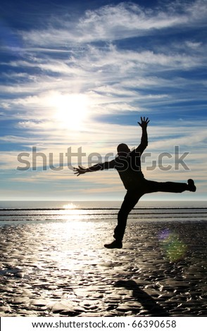 Man jumping high on the seashore