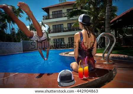 Man jumping in swimming pool and his girlfriend take a rest at resort. Low angle view from the swimming pool.