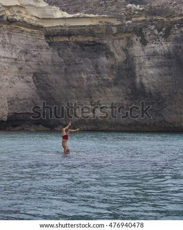 Man jumping in the water with rock background in Bahrija, Malta