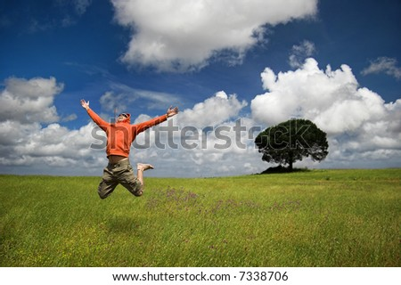 Man jumping on a green meadow with a beautiful cloudy sky