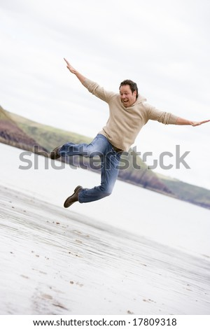 Man jumping on beach smiling - stock photo