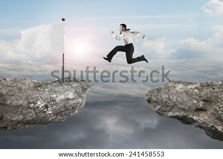 Man jumping on cliff with blank white flag and natural sunlight cloudscapes background