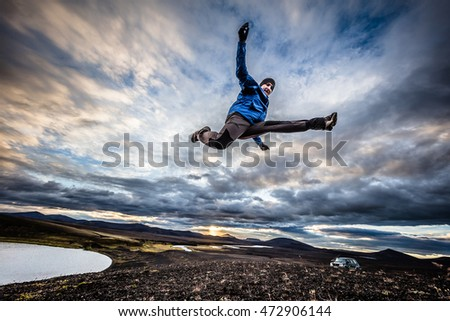 Man jumping on mountains background at sunset