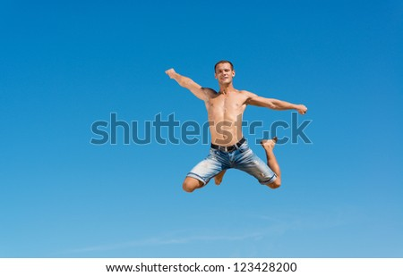 man jumping on the blue sky background, a good time - stock photo