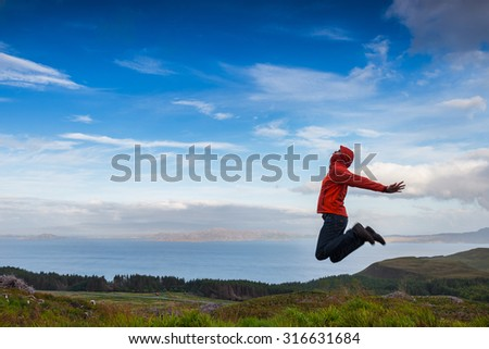 Man jumping on the top pf a mountain, Skye, Scotland