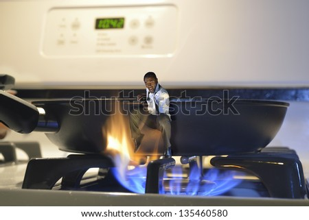 man jumping out of a frying pan and into the fire on a cooker - stock photo