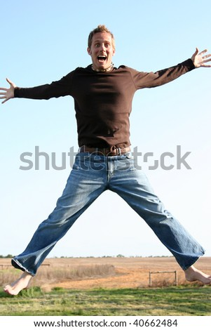 Man jumping outside against a blue sky