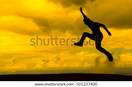 Man jumping over cliff with silhouette