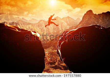 Man jumping over precipice between two rocky mountains at sunset. Freedom, risk, challenge, success. - stock photo