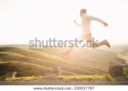 Man jumping over precipice between two stones on mountains at sunset