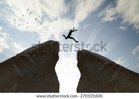Man jumping over rocks - stock photo
