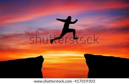 Man jumping over rocks with gap. Element of design.