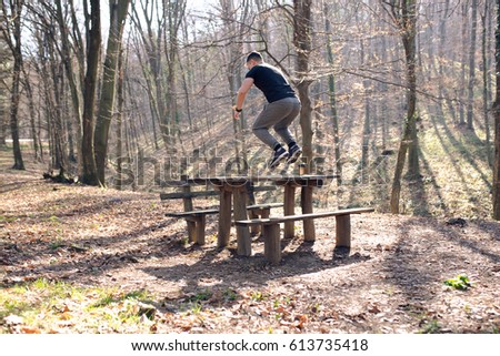 Man jumping over the bench, exercise in nature