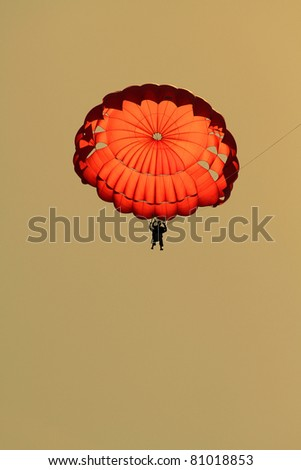 Man jumping with parachute in the warm sunset - stock photo