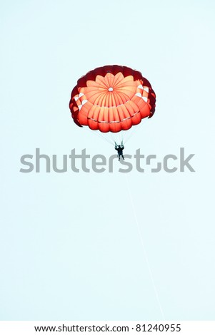 Man jumping with parachute over a blue sky - stock photo