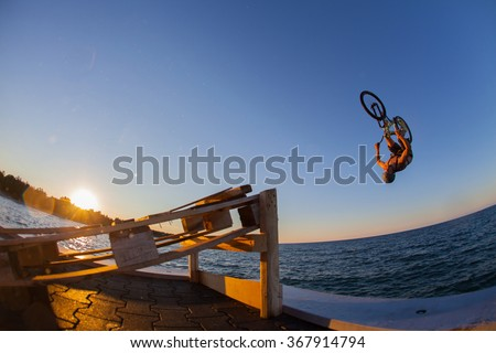 Man jumps a bicycle into the water from a pier - stock photo
