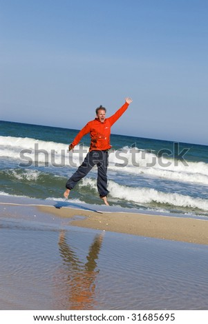 Man jumps in red t-shirt on sand on seeshore