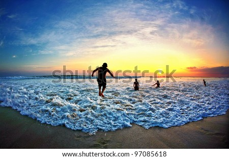 Man jumps over a wave during sunset on beach in Costa Rica