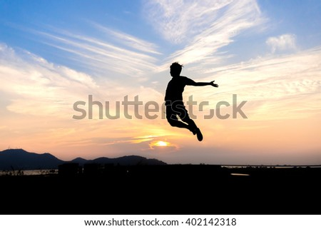 Man jumps silhouette During the sunset merrily